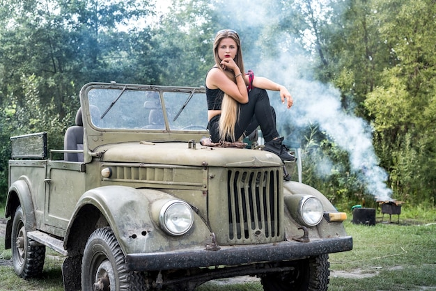 Woman standing in military car posing outdoors