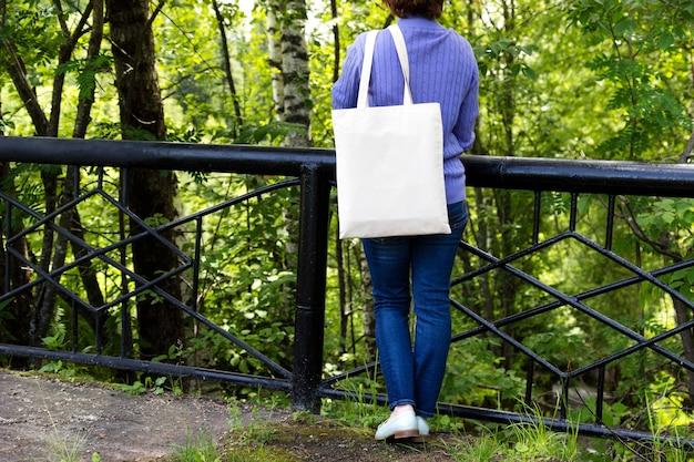 다리 난간 근처에 서있는 여자, 빈 재사용 가능한 쇼핑백 모형.
