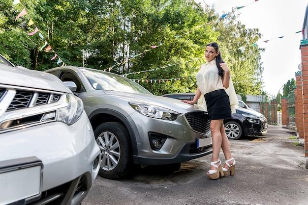車の近くに立ってポーズをとる女性