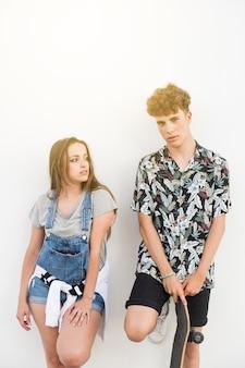 Woman standing near her boyfriend holding skateboard