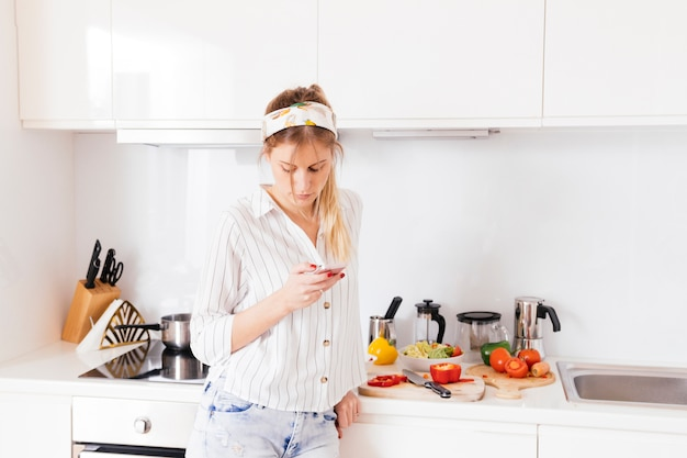 Woman standing near the kitchen worktop using mobile phone