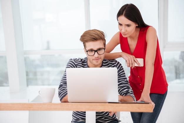Женщина, стоящая рядом с мужчиной, который сидит за столом с ноутбуком в офисе. окно на заднем плане