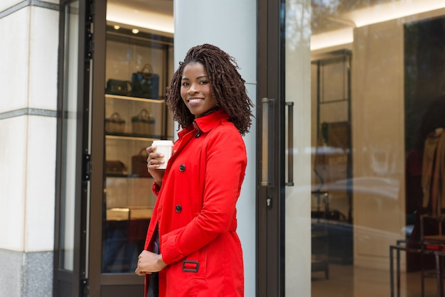 Woman standing near shop and smiling