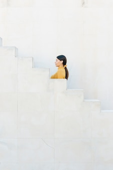 Woman standing near staircase with her eyes closed