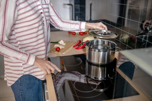 台所のストーブの近くに立っている女性