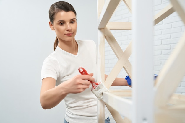 Woman standing near wooden rack with brush and white paint