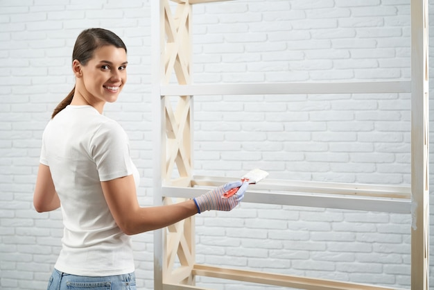 Woman standing near wooden rack with brush