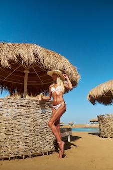 홍해에서 맑은 날에 모래 해변에 짚 지붕이있는 카바나 근처에 서있는 여자.