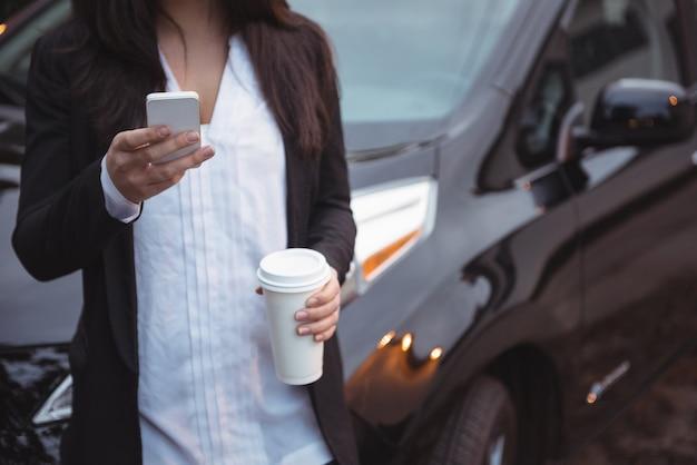 Женщина, стоящая рядом с автомобилем и использующая мобильный телефон