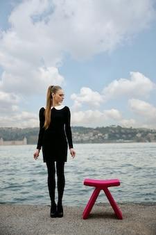 해변에서 분홍색 의자 옆에 서있는 여자
