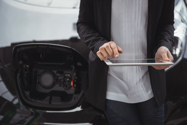 電気自動車の隣に立って、デジタルタブレットを使用している女性
