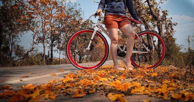 아름다운 오렌지 꽃 배경으로 가득한 palash 나무에서 야외에서 그녀의 자전거 옆에 서있는 여자