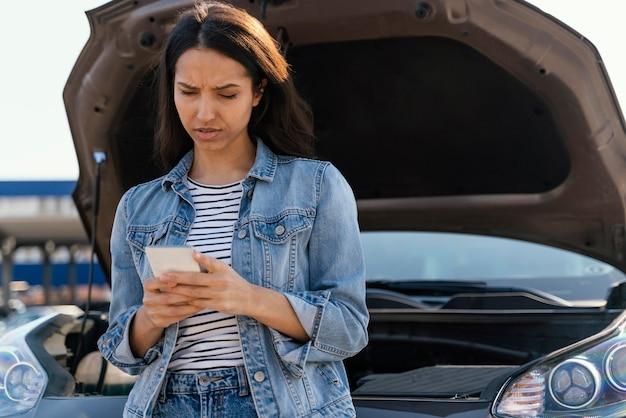 그녀의 깨진 된 차 옆에 서있는 여자