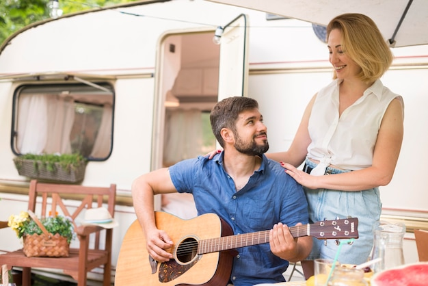 ギターを弾いている夫の隣に立っている女性