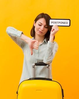 Женщина, стоящая рядом с ее багажом, держа отложенный знак