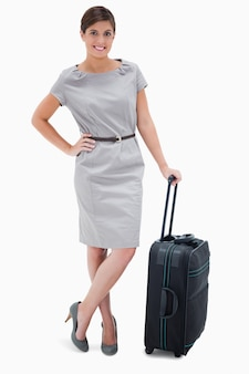 Woman standing next to wheely bag against a white background