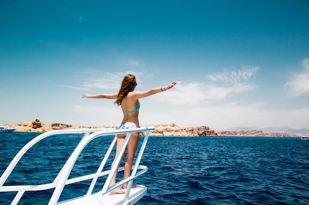 Donna in piedi sul naso dello yacht in una soleggiata giornata estiva, brezza che sviluppa i capelli,