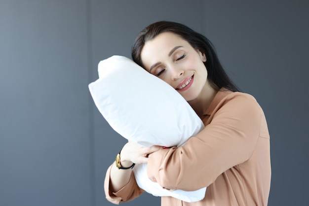 Woman standing in office with her head on pillow