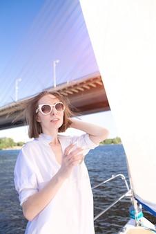 川と橋の背景に、ワインのグラスとヨットの上に立っている女性