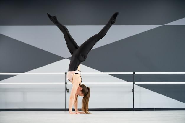 댄스 스튜디오에서 팔에 서있는 여자