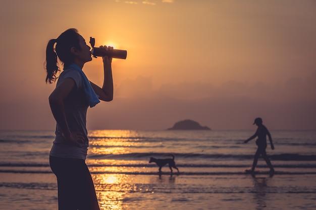 운동 후 해변에 서서 병에서 물을 마시는 여자 화려한 하늘