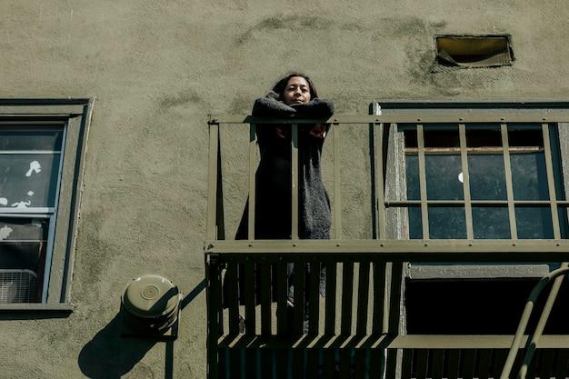 Женщина стоит на пожарной лестнице во время изоляции от коронавируса