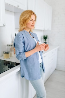 真っ白なインテリアのキッチンに立っている女性