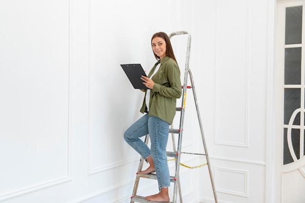 はしごに立っている女性のフルショット