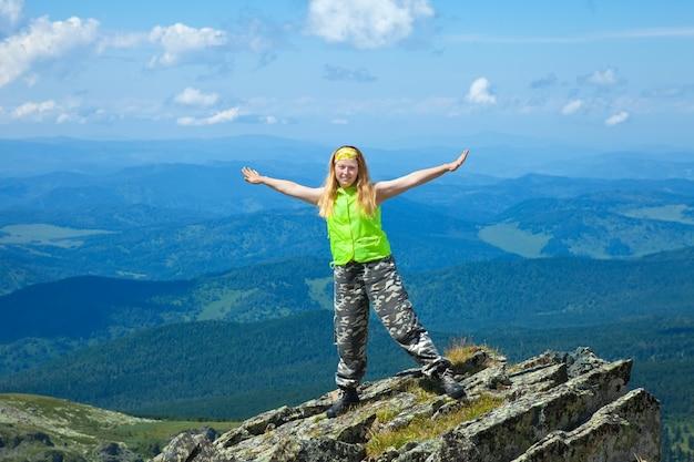 Женщина, стоящая на вершине горы