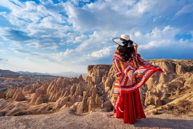 トルコ、カッパドキアの山に立っている女性。