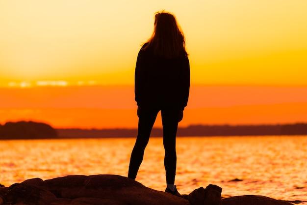 Женщина, стоящая на скале, глядя прямо. концепция природы и красоты. оранжевый закат. силуэт девушки на закате.