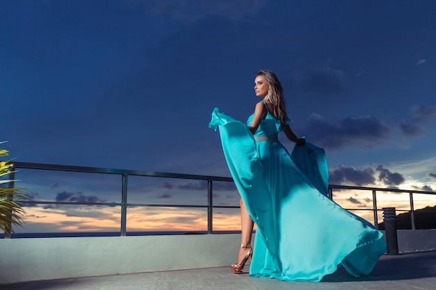 Женщина, стоящая на балконе, в нежном голубом платье, развевающемся на ветру