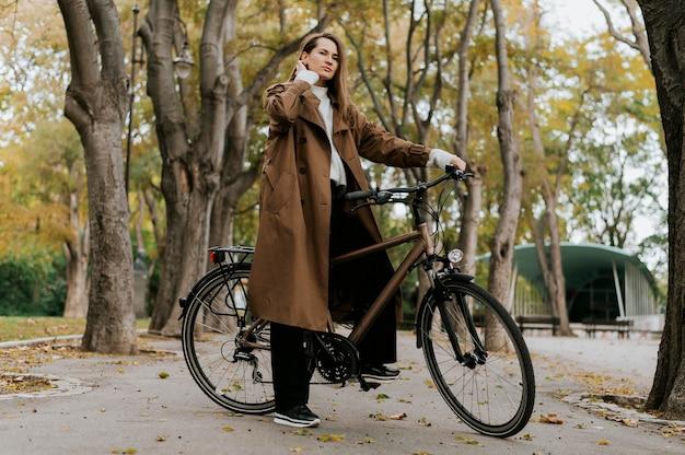 自転車のロングショットに立っている女性