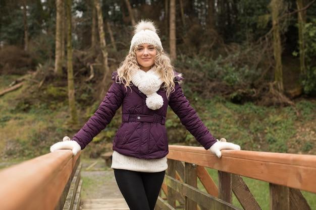 森の橋の上に立っている女性