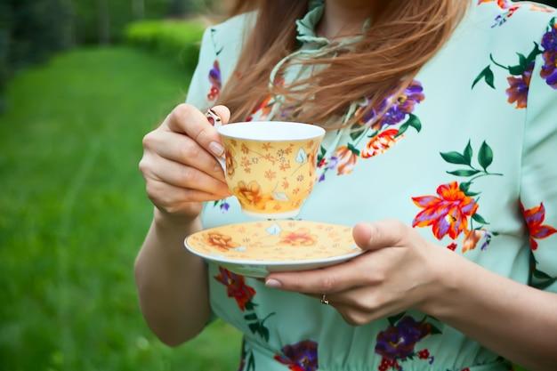 緑の芝生の上に立って、コーヒーや紅茶のカップを保持している女性
