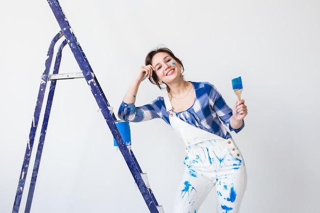 Женщина, стоящая на лестнице и смешивая краску на белом фоне.