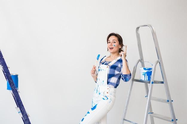 Женщина стоит на лестнице и красит стены.