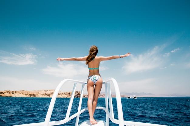 晴れた夏の日にヨットの鼻に立っている女性、そよ風が髪を育てる、