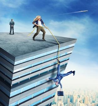 Женщина, стоящая на крыше высокого здания, спасает бизнесмена с веревкой