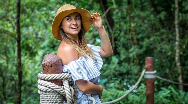 Женщина, стоящая на веревочном мосту Premium Фотографии