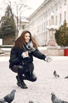 비둘기로 둘러싸인 거리에 서있는 여자