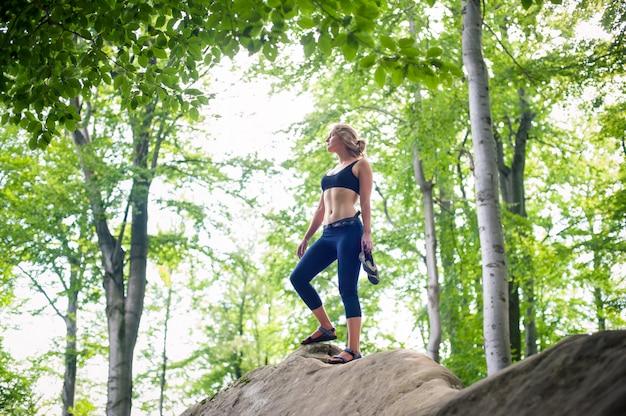 岩を登った後岩の上に立っている女性