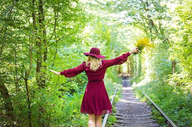 노란색 꽃의 꽃다발과 함께 숲에서 트랙에 서있는 여자
