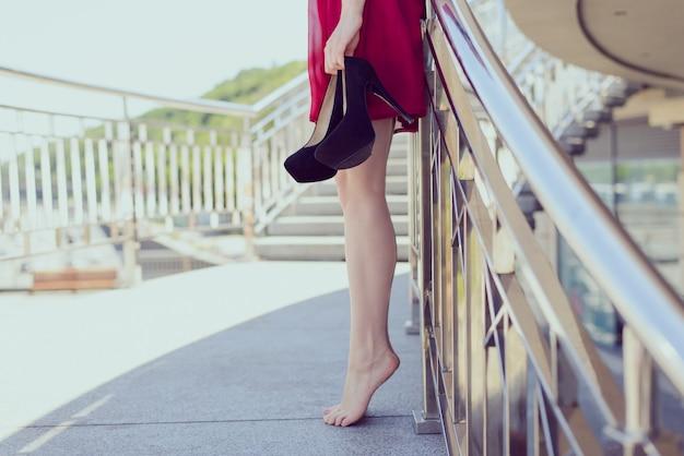 Женщина, стоящая на носках, держа в руке высокие каблуки