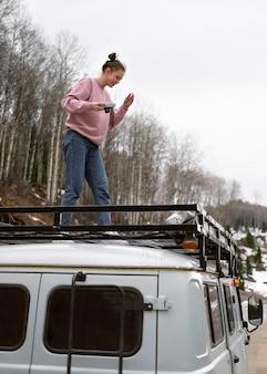 Женщина, стоящая на фургоне с полным выстрелом камеры