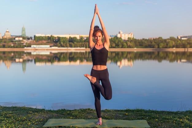 屋外でヨガの位置で瞑想に立っている女性。