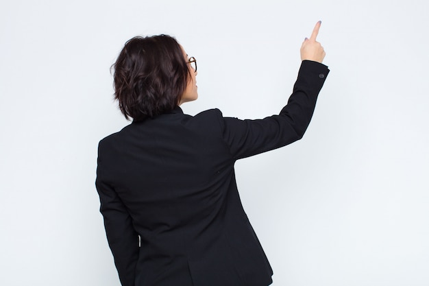 Woman standing and pointing to object on copy space, rear view