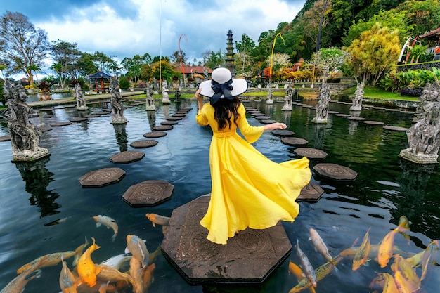 Woman standing in pond with colorful fish at tirta gangga water palace in bali, indonesia