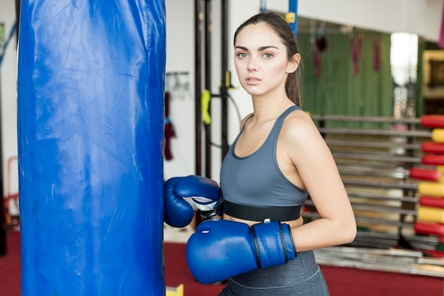 Woman standing at punch bag in gym