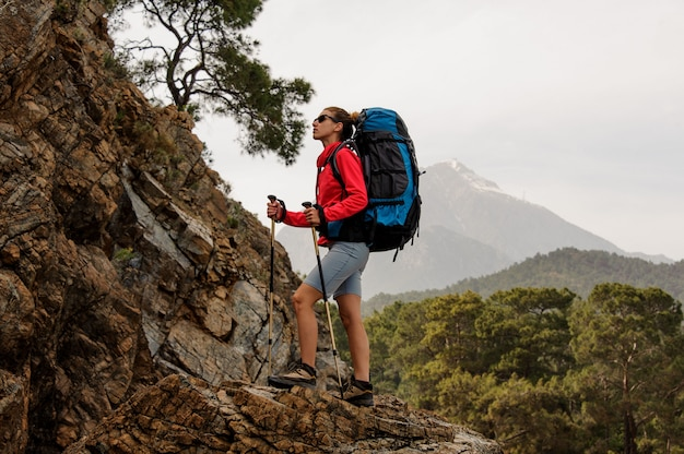 Woman standing on the rock with hiking backpack